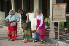 妇女在进入泰国寺庙前紧固他们的被借用的布裙 免版税库存照片