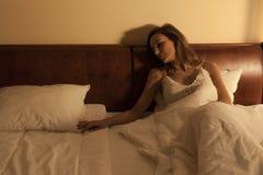 妇女在遭受充满渴望的床上 免版税库存图片