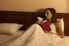 妇女在遭受充满渴望的床上 图库摄影