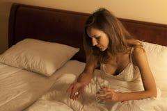 妇女在采取安眠药的床上 免版税库存图片