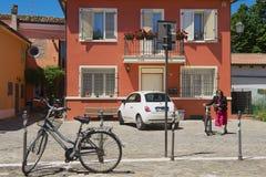 妇女在里米尼,意大利骑自行车 免版税库存图片