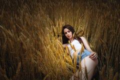 妇女在金黄麦田在 库存图片
