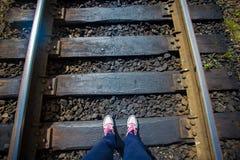 妇女在铁路路轨的` s腿有绿草的,第一人景色 图库摄影