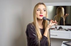 妇女在镜子前做构成 库存照片