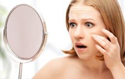 妇女在镜子粉刺和皱痕的锯 免版税图库摄影