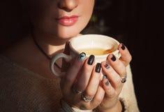 妇女在阳光下放松与茶 库存照片