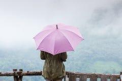 妇女在雨中的拿着一把伞 免版税库存图片
