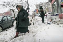 妇女在雪盖的街道上走 免版税库存图片