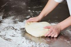 妇女在面包店揉面团,在从钢的一张桌上 运作的过程 库存照片