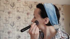 妇女在面孔上把基础音调的奶油放 影视素材