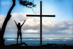 妇女在面对海洋的一幅大耶稣受难象旁边庆祝 图库摄影