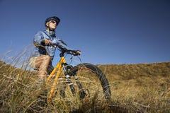 妇女在领域的骑马自行车 库存图片
