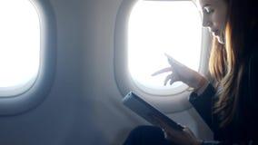 妇女在飞机的坐和听的音乐通过有耳机的片剂 股票录像