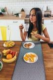 妇女在食用的厨房用桌上早餐用咖啡新月形面包和果子 库存照片