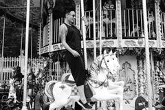 妇女在马坐转盘 库存照片