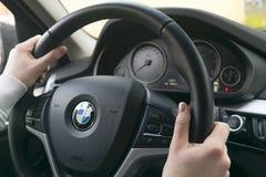妇女在驾驶BMW X5 F15的方向盘的` s手 拿着方向盘的手 现代汽车内部细节 库存照片