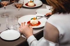 妇女在高级餐馆吃乳酪蛋糕用在一块板材的草莓酱 接近的视图 免版税库存图片