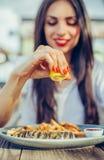 妇女在鱼的部分的挤压柠檬在餐馆 免版税图库摄影