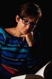 妇女在黑暗的阅读书 免版税图库摄影