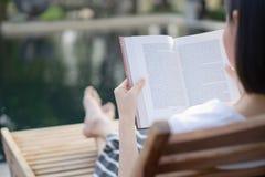 妇女在轻便折叠躺椅的阅读书 免版税图库摄影