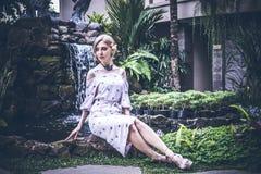 妇女在巴厘岛摆在,印度尼西亚一个热带庭院里  在背景的庭院瀑布 性感的少妇 库存照片