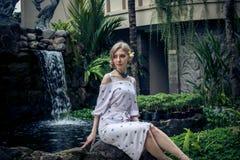 妇女在巴厘岛摆在,印度尼西亚一个热带庭院里  在背景的庭院瀑布 性感的少妇 免版税库存照片