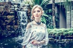 妇女在巴厘岛摆在,印度尼西亚一个热带庭院里  在背景的庭院瀑布 性感的少妇 图库摄影