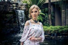 妇女在巴厘岛摆在,印度尼西亚一个热带庭院里  在背景的庭院瀑布 性感的少妇 库存图片
