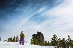 妇女在晴天去步行在冬天山 免版税库存图片