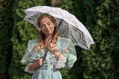 妇女在从太阳的一把伞下 免版税库存图片