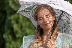 妇女在从太阳的一把伞下 免版税库存照片