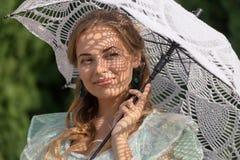 妇女在从太阳的一把伞下 库存照片