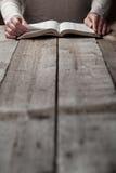 妇女在黑暗中的读圣经 库存照片