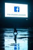 妇女在黑暗中走在标志下 免版税库存图片