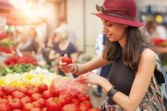 妇女在水果和蔬菜市场上 免版税图库摄影