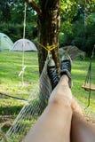 妇女在黑白鞋子的` s腿生动了描述休息在吊床 免版税库存图片
