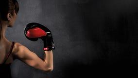 妇女在黑背景的拳击手二头肌 免版税库存图片