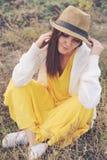 妇女在黄色礼服、白色球衣和帽子穿戴了坐秋天领域 图库摄影