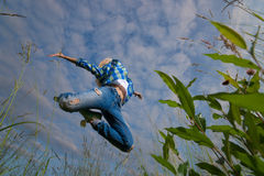 妇女在绿草领域跳 免版税库存照片