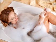 妇女在bathtube的洗涤腿 免版税库存照片
