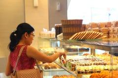 妇女在BreadTalk面包店采摘面包 库存图片