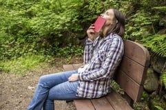 妇女坐一个长木凳在森林公园由道路和lo 免版税库存图片