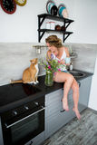 妇女坐一张桌在有一只红色猫的厨房里 图库摄影