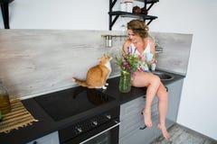 妇女坐一张桌在有一只红色猫的厨房里 免版税图库摄影