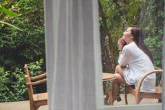 妇女坐一把木椅子在阳台上有绿色自然背景 免版税图库摄影