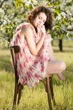 妇女坐一把椅子在春天庭院里 免版税库存照片