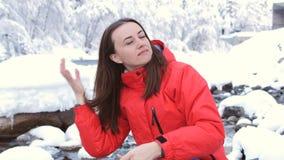 妇女坐一条山河的河岸在冬天森林里和梳头发 股票录像