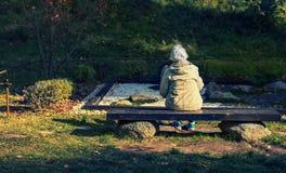 妇女坐一条长凳在公园 库存照片