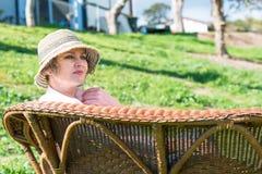 妇女坐一条长凳在公园 免版税库存照片