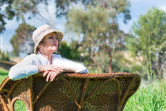 妇女坐一条长凳在庭院里 库存图片